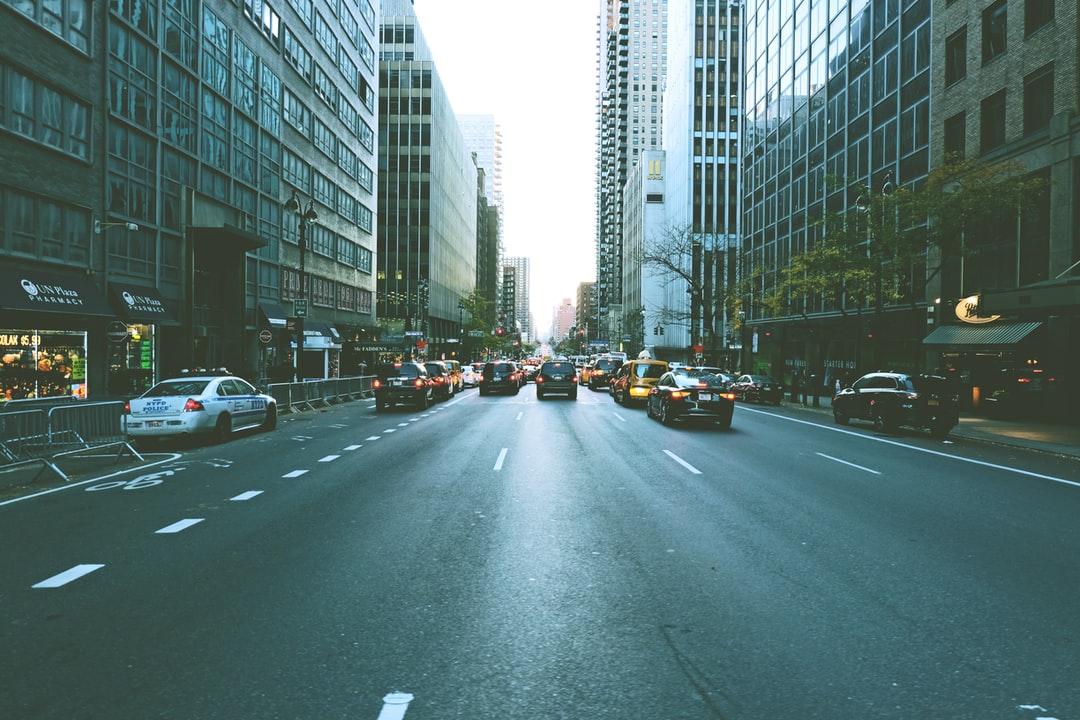 A view of a city street filled with traffic surrounded by tall buildings