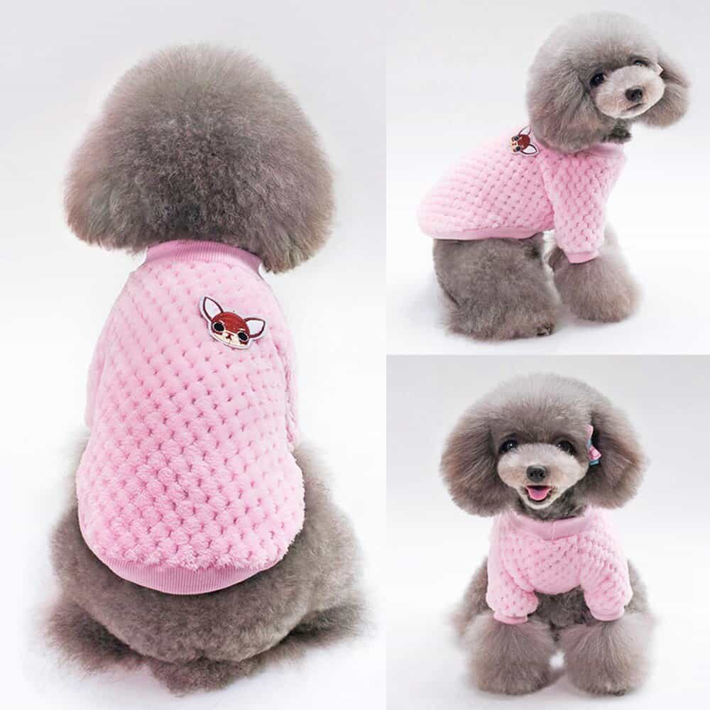 A pink teddy bear sitting on top of a stuffed toy